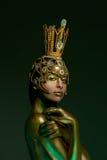 Princess Frog, with body art and original handmade golden crown. Close-up portrait of black-haired girl Princess Frog, with body art and original handmade golden Stock Photos