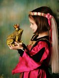 Princess and the frog prince. Portrait of a cute young preschool girl dressed as a princess in a pink and gold gown, posing and kissing a frog prince wearing a Royalty Free Stock Photo