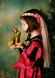 Princess and the frog prince. Portrait of a cute young preschool girl dressed as a princess in a pink and gold gown, posing and kissing a frog prince wearing a Royalty Free Stock Photos