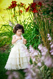Princess in the garden. Shot of a two year old wearing a long white princess dress in a flower garden Royalty Free Stock Images