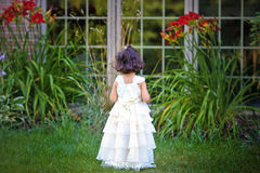 Princess in the garden. Shot of a two year old wearing a long white princess dress in a flower garden stock photography
