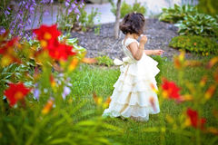Princess in the garden. Shot of a two year old wearing a long white princess dress in a flower garden Stock Photos