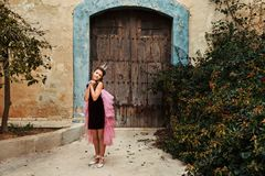 A sweet princess girl in a crown and a burgundy dress with a pink veil is pampered in front of an old house with an ancient wooden royalty free stock images