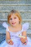 Princess girl eating chocolate sandwich. Blond children girl eating chocolate sandwich princess dress on granite stairs Stock Photo