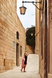 The princess girl is lost in the old streets of the castle town of yellow stone looking at the old-fashioned lantern. Princess girl is lost in the old streets of Royalty Free Stock Image
