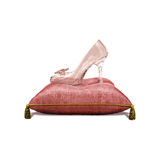 Princess Glass Slipper on Pillow. Fairy tale iconic princess glass slipper shoe heel on royal satin pillow isolated on white magical Royalty Free Stock Photo