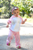 Princess Jogger. A little girl dressed in a pink princess jogging suit.  She's stepping Stock Photography