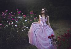 Princess in a long pink dress walking on the rosary. Young beautiful girl in a fabulous dress among the flowers.