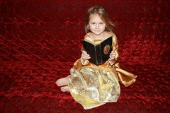 Princess with an old book. Smiling barefoot girl in golden princess dress with an old book sitting on red Royalty Free Stock Image