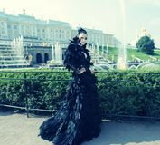 Princess in the park next to the fountain. And palace Royalty Free Stock Photo