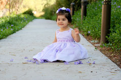 Princess in purple. A little princess sitting on a path wearing purple dress and flowers Stock Photos