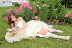 Princess reads book. Princess in white-golden gown reads book under rosebushes Stock Photo