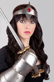 Princess with a sword. Princess wearing a crown and holding a sword royalty free stock image