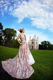 Princess in an vintage dress before castle. A woman like a princess in an vintage dress before the magic castle stock photography