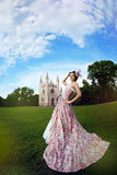 Princess in an vintage dress before castle. A woman like a princess in an vintage dress before the magic castle royalty free stock image