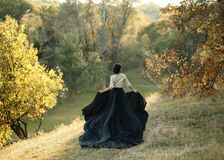 Princess in a vintage dress. Walk along the picturesque autumn hills at sunset. A long train of black skirt fluttered on the run. royalty free stock photo