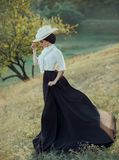 The princess in a vintage dress and wearing a white hat with feathers walking along the slopes of the hills. The wind. Waved her long black skirt with a train stock images