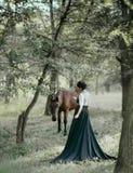 Princess w rocznik sukni z długim pociągiem, chodzi z koniem Fotografia brunetki dziewczyna z plecy bez twarzy Plecy zdjęcie royalty free