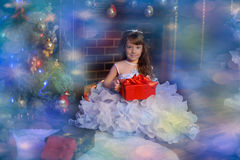 Princess in a white dress with blue next to the tree with a gift Royalty Free Stock Image