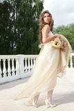 Princess in white-golden gown. Long-haired princess in white-golden gown with loved toy on background banisters stock photos