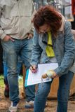 Mature baby boomer woman signing a petition for Moms Demand Action on gun control at a street fair. Princeton, New Jersey - April 28, 2019: Mature baby boomer stock images