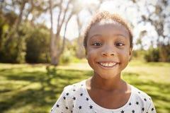 Principal al aire libre y hombros tirados de chica joven en parque Fotos de archivo libres de regalías