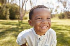Principal al aire libre y hombros tirados de muchacho joven en parque Fotografía de archivo libre de regalías