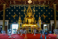 Principal buddha image in shinning golden color sitting in the decorative main hall with apostle monk image standing on both sides Stock Photo