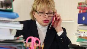 Principal contable de la mujer mayor en vidrios y con smartphone rojo almacen de metraje de vídeo