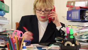 Principal contable de la mujer mayor en vidrios y con smartphone rojo metrajes
