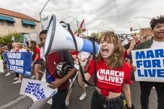 Principale foule de jeune femme avec le mégaphone à la protestation de violence armée photos libres de droits