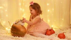 Principessa della bambina nel vestito, nelle scarpe dorate che giocano con le zucche video d archivio
