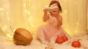 Principessa della neonata nel vestito, nelle scarpe dorate che giocano con le zucche stock footage