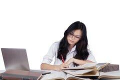 Principiante adolescente que estudia con los libros y el ordenador portátil Imágenes de archivo libres de regalías