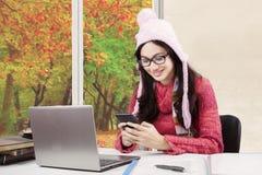 Principiante con el suéter usando smartphone Fotos de archivo libres de regalías
