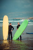 Principiante e instructor de la persona que practica surf en una playa con tableros que practican surf Foto de archivo libre de regalías