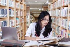 Principiante femenino que hace la asignación en biblioteca Foto de archivo libre de regalías