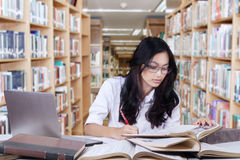 Principiante femminile che fa assegnazione in biblioteca Fotografia Stock Libera da Diritti