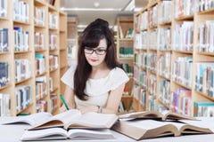 Principiante listo que hace tarea de la escuela en biblioteca Foto de archivo