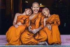 Principiantes budistas que sentam junto o sentimento feliz e o sorriso imagem de stock