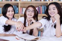 Principianti femminili che si prendono per mano nella biblioteca Fotografie Stock Libere da Diritti