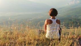 Principio del día: la chica joven resuelve el sol en el top de la colina almacen de metraje de vídeo
