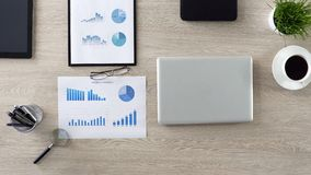 Principio del día laborable, lugar de trabajo vacío del hombre de negocios con los gráficos y ordenador portátil foto de archivo libre de regalías