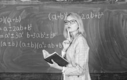 Principles can make teaching effective. Woman teaching near chalkboard in classroom. Effective teaching involve royalty free stock photo