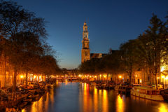 Prinsengracht Canal in Amsterdam, Netherlands. Evening scene of Prinsengracht Canal in Amsterdam, The Netherlands with the Westerkerk (western church) reflecting Royalty Free Stock Photos