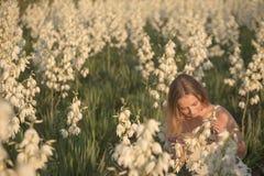 Prinses Het jonge mooie mooie vrouw stellen in de lange kleding van de avondluxe tegen struiken met witte bloemen Stock Foto