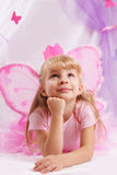 Prinsesmeisje die in roze kroon en vlindervleugels wensen maken Stock Foto
