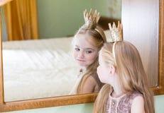 Prinsesmeisje het schilderen make-uplippenstift op spiegel stock foto