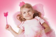 Prinsessaflicka som ligger med rosa fjärilsvingar Arkivbild