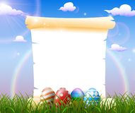 Blank paper in the grass field with decorated Easter eggs royalty free stock images